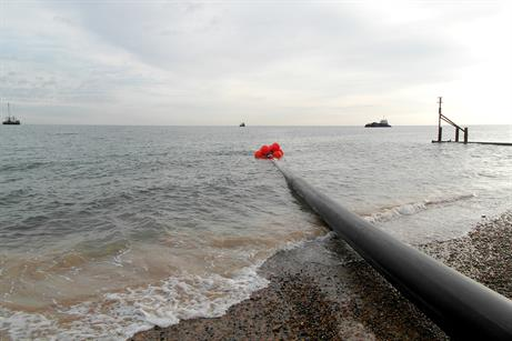 One of the pipes being pulled by tug boats from the beach