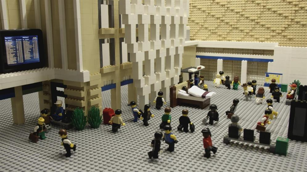 Lenny Henry asleep in bed in a Lego station