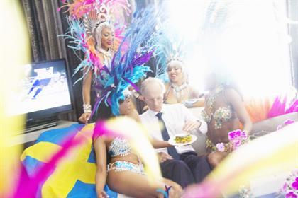 Sven Goran-Erikson eyes a gourmet-looking fish finger sandwich while surrounded by carnival dancers.