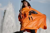 Orange to give away rain ponchos designed by V V Brown at Glastonbury
