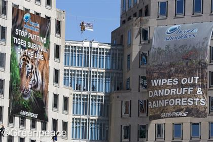 Greenpeace: activitsts hang P&G ad parodies from the company's headquarters