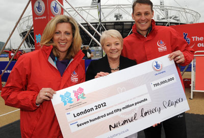 Dianne Thompson (centre), chief executive of Camelot, hands a cheque for £750m to former Olympian Sally Gunnell and former Paralympian Danny Crates