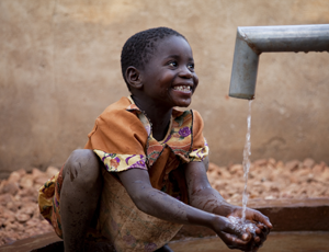 A child plays in clean water from a new handpump in Zambia [WaterAid/ Anna Kari]
