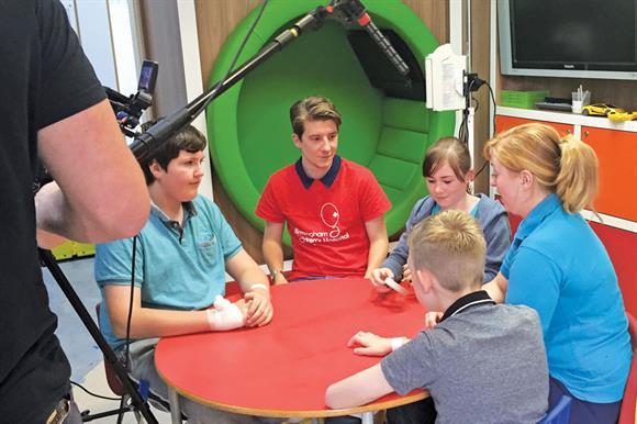 Luke Cameron (red shirt) being filmed while at Birmingham Children's Hospital Charity