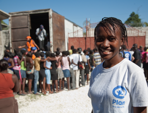 A Plan volunteer overseeing food distribution in post-quake Haiti