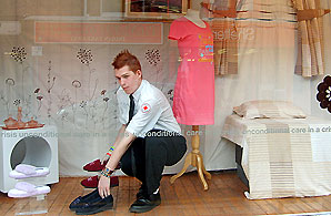A Red Cross Volunteer mans a charity shop