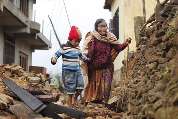 Jagot Kumari Rana, 79, is led through the rubble of collapsed homes by her grandson Sogat Rana, 7, in Paslang village near the epicenter of Saturday's massive earthquake in the Gorkha District of Nepal (pic credit: Wally Santana/AP/Press Association