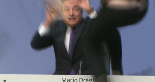 European Central Bank President Mario Draghi tries to dodge a 'confetti attack' on Wednesday