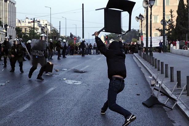 A rioter throws a chair at police officers during a protest over the Austerity Bill vote in Athens last May (pic credit: Athena Pictur/REX/Shutterstock)