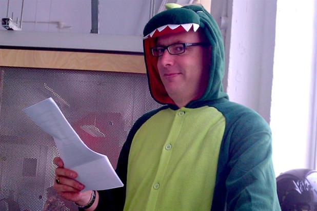 Kevin Chesters poses in his dinosaur suit