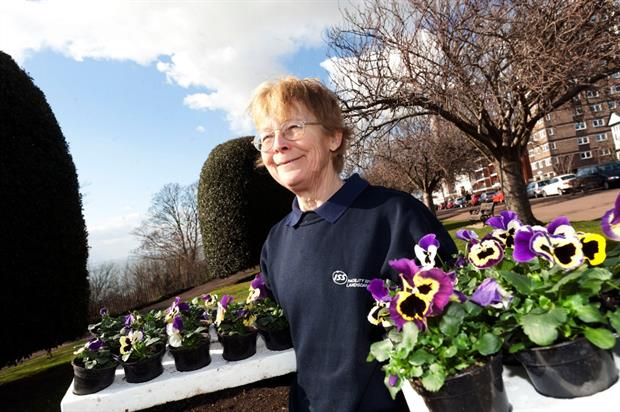 An ISS staff member with pansies ready for planting. Image: ISS
