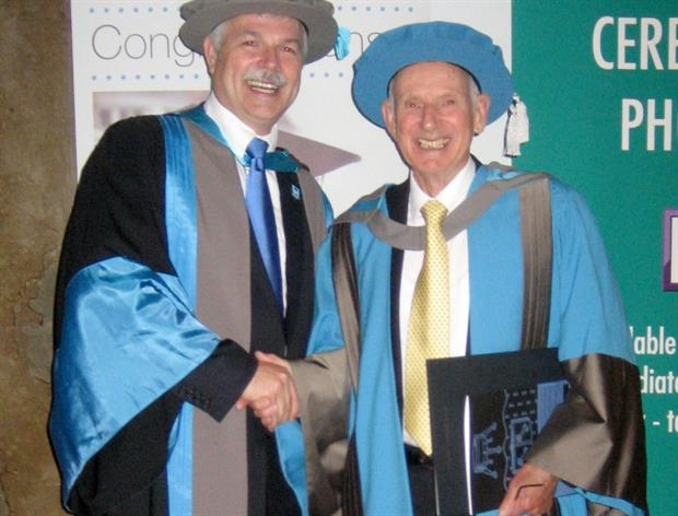 Colin Squire (right) receiving his honorary degree from Ron Tuninga (left), Kingston University's Dean of the Faculty of Business and Law