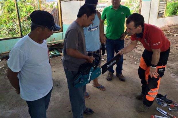 Residents of the typhoon-hit Phillipines learning chainsaw skills from DART team. Image: Supplied