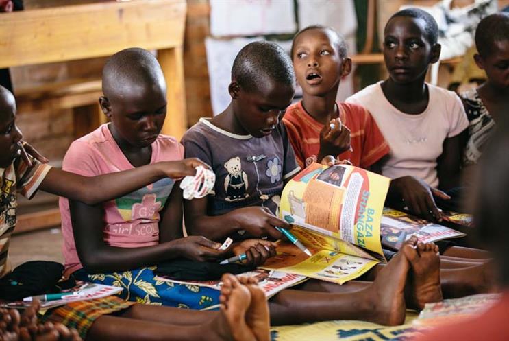 Girls enjoying Ni Nyampinga magazine, which reaches 100,000 girls across Rwanda