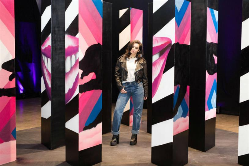 Charli XCX stands next to the artwork inspired by her tweet