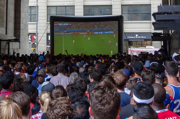 New Yorkers crowd around an outdoor TV screen to watch 2014 World Cup games. (Photo courtesy Dennis via Flickr)
