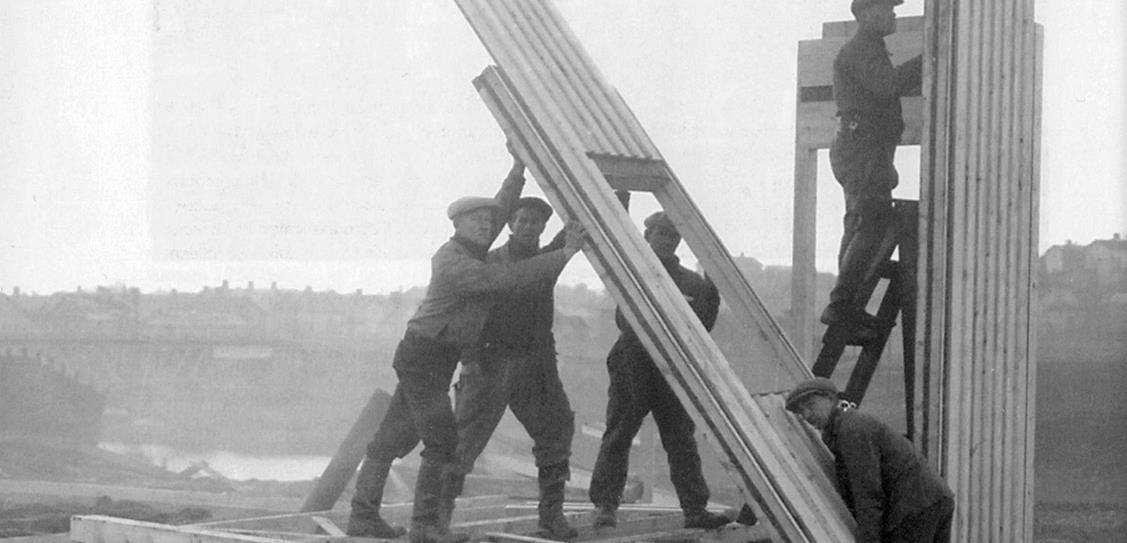 Workmen erect a Puutalo house on a site in Finland using pre-fabricated panels. These elements arrived from the factory with their exterior cladding already installed. Photo from 1940.