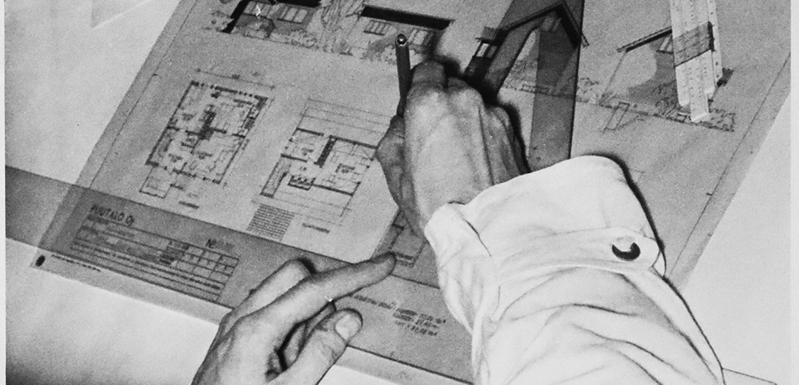 A draughtsman finishes work on a sheet of drawings in the early 1950s at the Helsinki office of the Puutalo company.