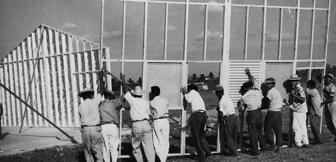 Workmen carry a frame panel for a Puutalo house in northern Colombia where some 1,500 houses were constructed from 1955 to 1957 as dwellings for workers. These Puutalo homes can still be found throughout the Simón Bolívar neighborhood of Barranquilla today. Photo from 1956.
