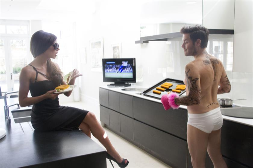Becks, complete with pants and fluffy pink oven gloves, serves Posh fish fingers.