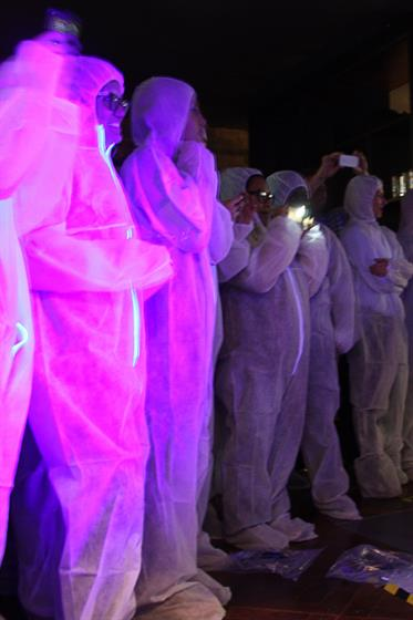 Guests wearing protective plastic suits