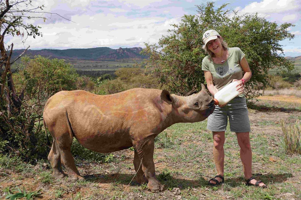 Cathy Dean feeds MeiMei the baby rhino