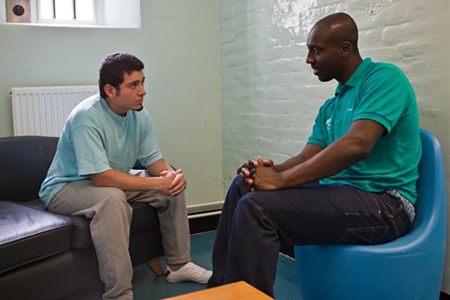 A Pact worker (right) reassures an offender on his first night behind bars