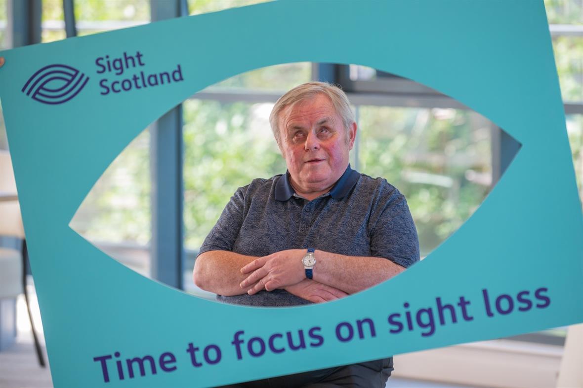 Braille transcription reader Jim McCafferty with Sight Scotland's new logo
