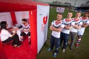 Wakefield rugby players line up outside Public Health England's pop-up health pods