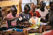 Girls enjoying Ni Nyampinga magazine, which reaches 100,000 girls across Rwanda