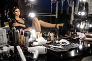 Kendall Jenner sits at a table filled with products from Maybelline and Toni & Guy