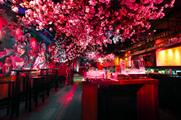 The installation features a series of handmade cherry blossom trees