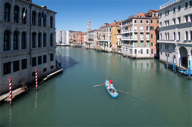 A boat makes its way along the empty canals of Venice