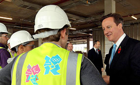 Prime Minister David Cameron speaks to apprentice construction workers at the Olympic Park site in Stratford, East London, yesterday.