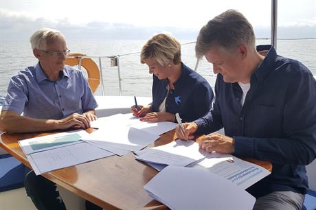 Mayor of Hiiu Reili Rand (centre) and Nelja Energia chairman Martin Kruus (right) sign the agreement