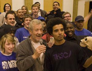 Sir Ian McKellen, with mike, puts his hand on Akala's shoulder