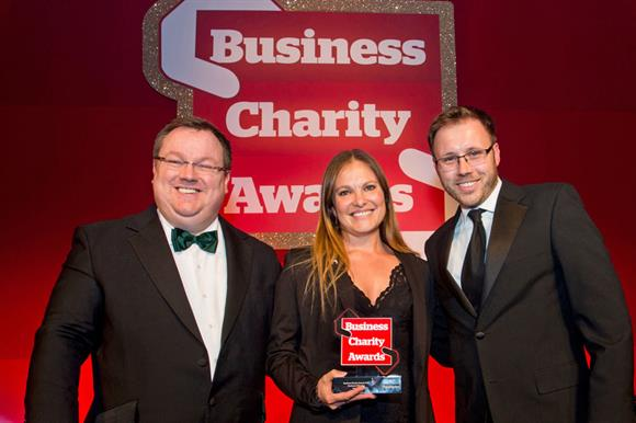 Susie Steyn, corporate sustainability manager at Investec, receives the Business of the Year Award from host Declan Curry (left) and Third Sector editor Andy Hillier