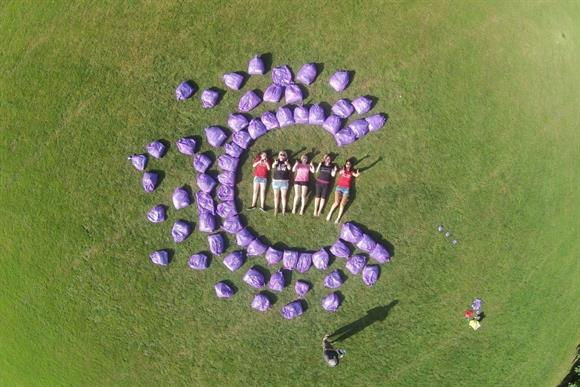 Slimming World consultants pose with clothes collection bags in the shape of the CRUK logo