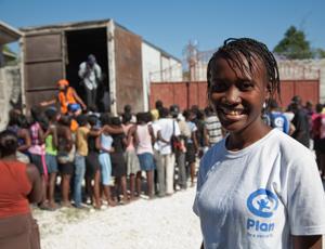 A Plan volunteer overseeing food distribution in post-quake Haiti