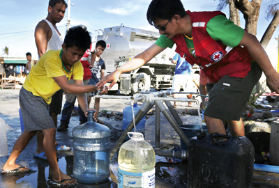 Red Cross workers deliver clean water to survivors at a medical centre in Tacloban