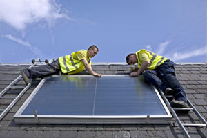 Workmen installing a solar thermal panel after receiving advice from the Energy agency, Ayrshire