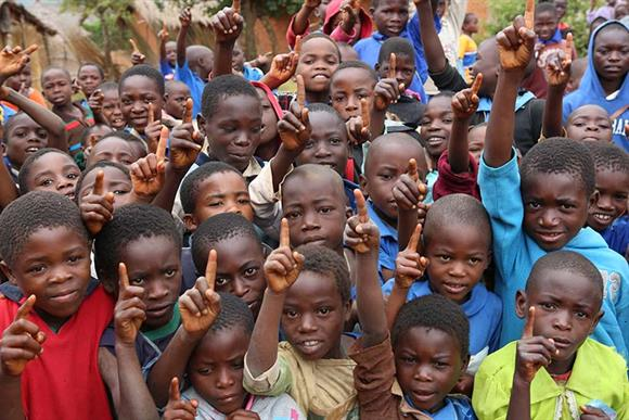 "Children in Malawi make the ""Put Children First"" sign with their hands for the Glasgow Commonwealth Games. Unicef/2014/Matas"