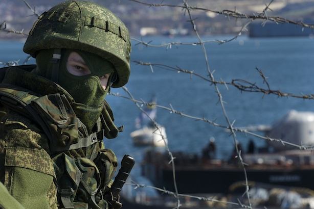 Tensions: Russian soldiers guard a pier where two Ukrainian naval ships are moored, in Sevastopol, Ukraine, on Wednesday, March 5, 2014 (AP Photo/Andrew Lubimov)