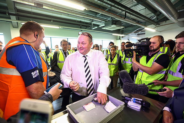 Sports Direct boss Mike Ashely flashes the cash as he demonstrates the security checking procedures at his warehouse yesterday (pic credit: Chris Ratcliffe/Bloomberg via Getty Images)