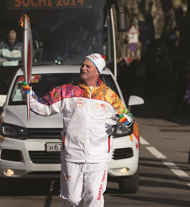 Jon Tibbs, chairman and founder of JTA, runs with the Olympic torch through the streets of Sochi