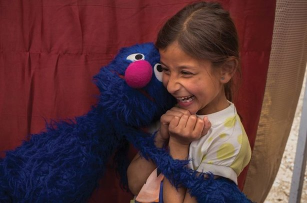 Grover the Sesame Street muppet meets a refugee child in Jordan