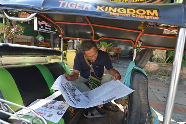A tuk tuk driver gets his daily news in print, Thailand