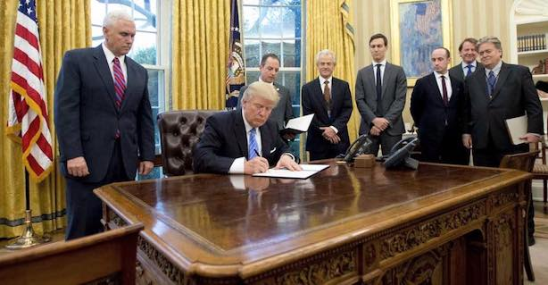 President Donald Trump signs an executive order in the Oval Office. (Image via the White House Facebook page).