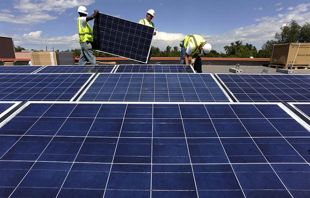 Workers install solar PV on a school in Denver, in the US. In the EU, community energy groups are worried that draft changes to state aid rules may make it harder for them to operate. Photo: Helen H. Richardson/The Denver Post via Getty Images