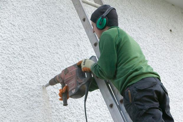 A builder installs cavity wall insulation in a house in Cumbria, UK. Investment in energy efficiency would have an immediate impact of job creation, the European Commission has said. Photo: Ashley Cooper/Construction Photography/Getty